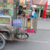Baby in cage on back of vendors tuk tuk