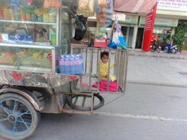 Baby in cage on back of vendors tuk tuk
