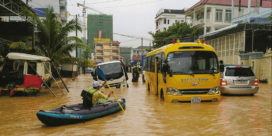 Flooding in Sihanoukville. Man paddles a canoe down the road.